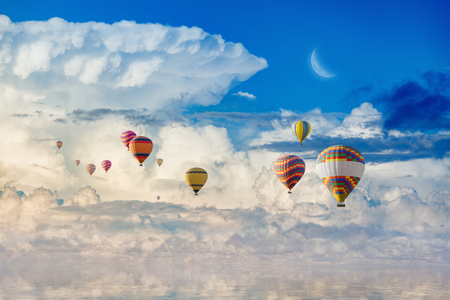 Idyllic heavenly picture - colorful hot air balloons flying in blue sky with white clouds and crescent above serene sea.