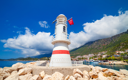 White lighthouse with red turkish flag in Kas, Antalya Province of Turkey in sunny day