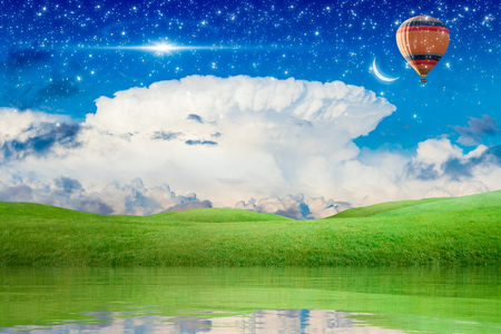 Idyllic peaceful background - hot air balloon rise up into blue starry sky above green meadow to new moon, bright stars in sky. Dream come true concept. Stock Photo