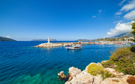 White lighthouse, sightseeing ship in clear blue sea in Kas, Antalya Province of Turkey in sunny day Stock Photo
