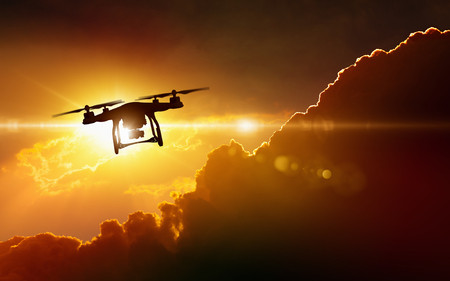 Modern technological background - silhouette of flying drone in glowing red sunset sky