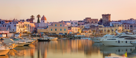 Beautiful panoramic view of the city streets with the buildings reflected in the serene sea of Forio, Ischia island, Italy during sunset