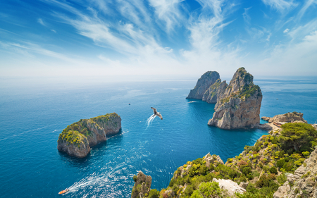 Aerial view of famous Faraglioni rocks from Capri island, Italy. Sunny summer weather with blue sky and white clouds.