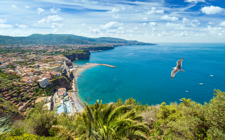 Daylight view of rocky coastline Sorrento and Gulf of Naples - popular tourist destination in Italy. Sunny summer day with blue sky, clear sea and green mountains of Sorrento peninsula.
