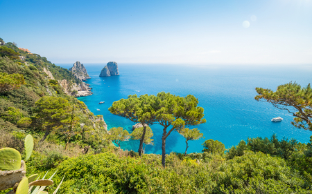 Daytime view of famous Faraglioni rocks from Capri island, Italy. Sunny summer weather with clear blue sky. Archivio Fotografico