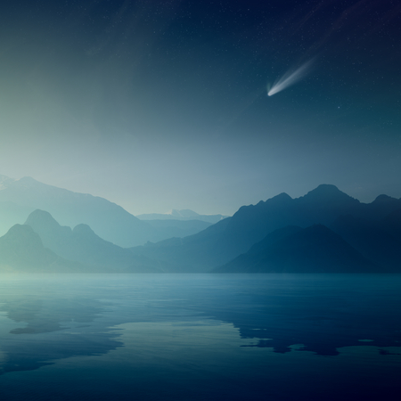 Beautiful mysterious nature background. Bright comet and stars in dark blue sky, silhouettes of mountains reflected in a calm sea