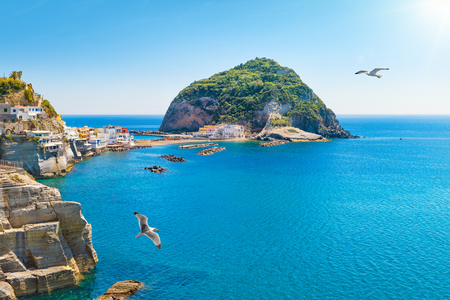 Marina with boats, small beach, cafes and hotels, giant green rock near SantAngelo on Ischia island, Italy. SantAngelo is small village within comune of Serrara Fontana, Ischia.