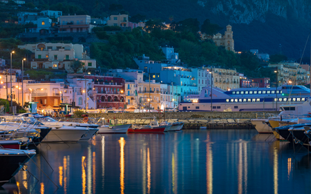 Night view of Marina Grande, Capri island, Italy. Illuminated streets of city are reflected in calm sea. Stock Photo