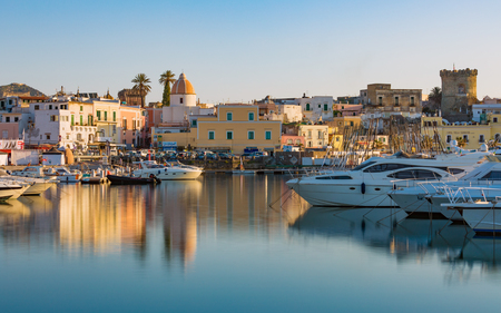 Ischia, Italy - April 20, 2018: Sunset view of Forio, Ischia island, Italy. Town streets with church, castle of Forio are reflected in serene sea. Editorial