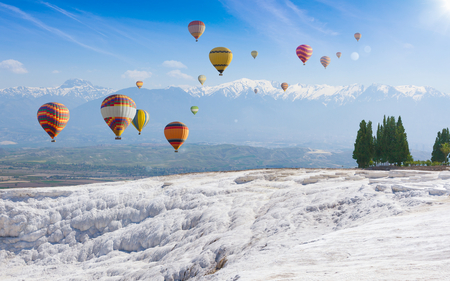 Collage with hot air ballons flying above snowy white Pamukkale in Turkey. Pamukkale is geological phenomenon, literally