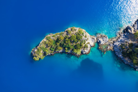 Aerial view of small rocky island with green trees in lagoon near Oludeniz, Fethiye district, Turkey.