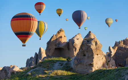 Colorful hot air balloons are flying in clear blue sky above unusual rocky landscape in Cappadocia. Limestone conical rocks with hand carved rooms near Goreme, Cappadocia, Turkey.