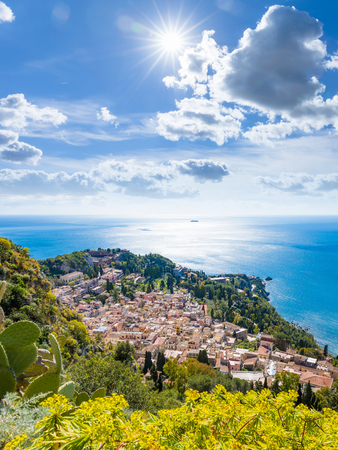 Aerial view of Taormina, Sicily, southern Italy. Beautiful paradise picture with bright sun in blue sky, azure sea and green tropical plants in summer day.