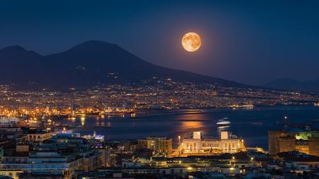 La luna piena sorge sopra il Vesuvio, Napoli e il Golfo di Napoli, Italia. Chiaro di luna riflesso nel mare calmo. Archivio Fotografico
