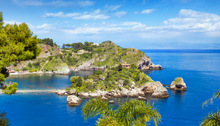 Isola Bella is small island near Taormina, Sicily, southern Italy. Narrow path connects Isola Bella island to mainland beach of Taormina surrounded by azure waters of Ionian Sea. Stock Photo
