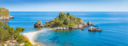 Panoramic view of Isola Bella small island near Taormina, Sicily, southern Italy. Narrow path connects Isola Bella island to mainland beach surrounded by azure waters of the Ionian Sea.