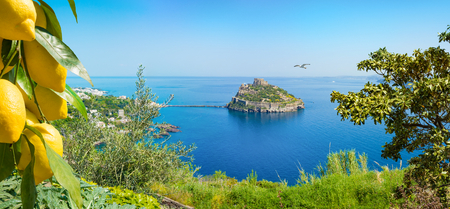 Panoramic view of Ischia Island and famous landmark and tourist destination Aragonese Castle or Castello Aragonese, Italy. Ripe yellow lemons in foreground. Stock Photo
