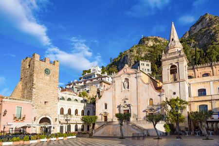Morning view of square Piazza IX Aprile with San Giuseppe church and Clock Tower in Taormina, Sicily, Italy