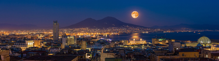 Panoramic sityscape with full moon rises above Mount Vesuvius, Naples and Bay of Naples, Italy. Moonlight reflected in calm sea. Elements of this image furnished by NASA.