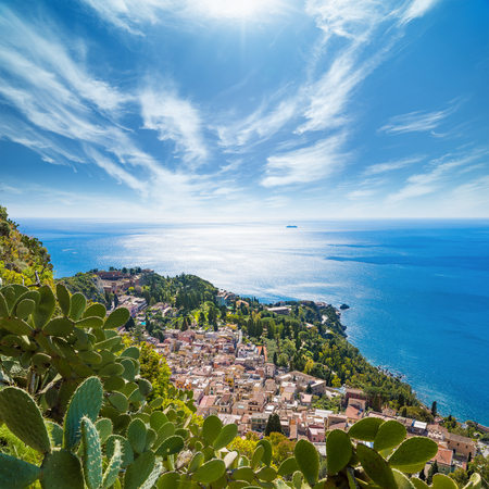 Aerial view of Taormina located in Metropolitan City of Messina, on east coast of Sicily island, Italy. Beautiful image of bright sun in blue sky, azure sea and green tropical plants in summer day.