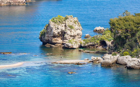 Narrow path connects Isola Bella island to mainland Taormina beach surrounded by azure waters of Ionian Sea, Sicily, Italy 写真素材