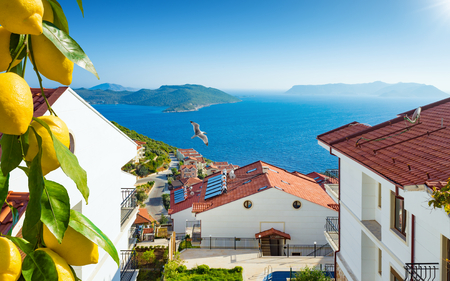 Beautiful white houses with tile roofs in resort city at sea, real estate with amazing sea view. Ripe yellow lemons in foreground. Stock Photo