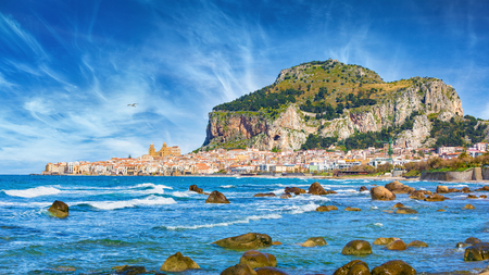 Daylight view of Cefalu, town in Italian Metropolitan City of Palermo located on Tyrrhenian coast of Sicily, Italy. Cefalu is popular travel destination in Europe because of long beach and clear sea. Stock Photo