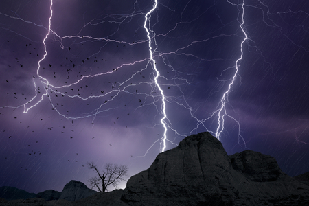 Powerful lightnings in dark stormy sky above mountains, weather forecast concept, climate change background Stock Photo