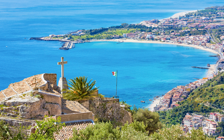 Church of Madonna della Rocca built on rock in Taormina, blue Gulf and beach of Giardini-Naxos, Sicily, Italy. Stock Photo