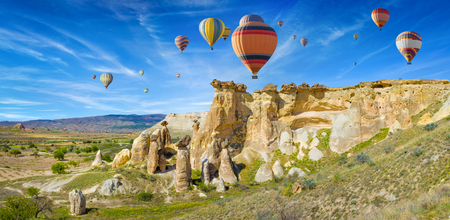 Colorful hot air balloons flyi in blue sky above unusual rocky landscape in Cappadocia near Goreme, Turkey