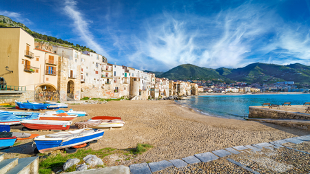 Fishing boat on long sandy beach near clear blue sea in Cefalu, town in Italian Metropolitan City of Palermo located on Tyrrhenian coast of Sicily, Italy.
