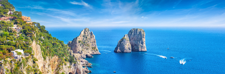 Panoramic view of famous Faraglioni Rocks, most visited travel attraction near Capri Island, Italy. Beautiful paradise landscape with azure sea in summer sunny day.