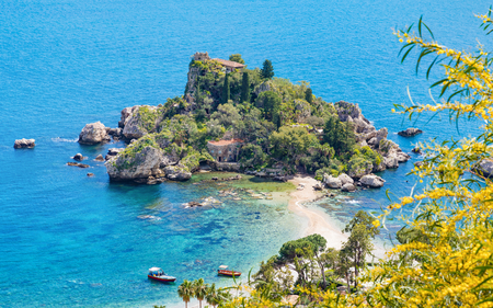 Aerial view of Isola Bella small island near Taormina, Sicily, Italy. Narrow path connects island to mainland Taormina beach surrounded by azure waters of the Ionian Sea.