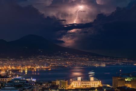 Powerful lightning in dark stormy sky above Mount Vesuvius, Naples and Bay of Naples, Italy.