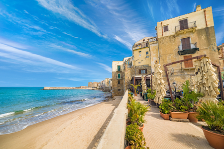 Cafes and houses on long sandy beach near clear blue sea in Cefalu, town in Italian Metropolitan City of Palermo located on Tyrrhenian coast of Sicily, Italy.