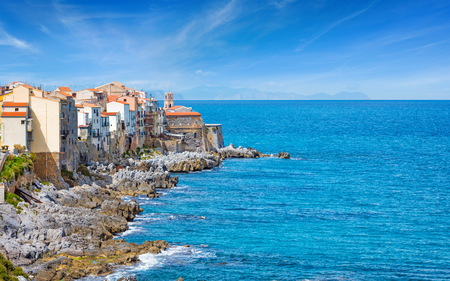 Bastione Capo Marchiafava and colourful houses on rocky coast of Cefalu, small resort city in Italian Metropolitan City of Palermo located on Tyrrhenian coast of Sicily, Italy Stock Photo