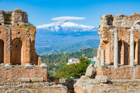 Ruins of Ancient Greek theatre in Taormina on background of Etna Volcano, Italy. Taormina located in Metropolitan City of Messina, on east coast of island of Sicily.