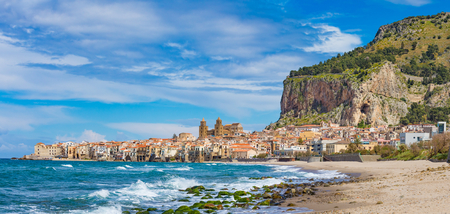 Long sandy beach and wavy blue sea in Cefalu, town in Italian Metropolitan City of Palermo located on Tyrrhenian coast of Sicily, Italy. Cefalu is popular travel destination in Europe.