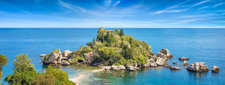 Panoramic view of Isola Bella small island near Taormina in Sicily, Italy. Narrow path connects island to mainland Taormina beach surrounded by azure waters of the Ionian Sea.