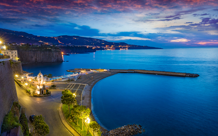Sunset view of cliff coastline Sorrento with comfortable beaches and Gulf of Naples, Italy.