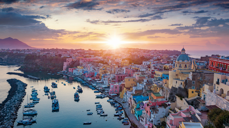 Aerial sunset view of beautiful Procida. Colorful houses, cafes and restaurants, fishing boats and yachts in Marina Corricella, glowing sky and serene sea in Procida Island, Italy. Stock Photo