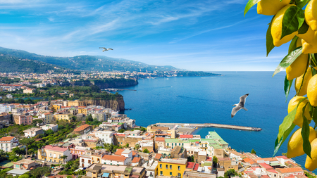 Panoramic aerial view of cliff coastline Sorrento and Gulf of Naples, Italy. Ripe yellow lemons in foreground. In Sorrento lemons are used in production of limoncello. Stock Photo