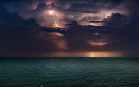 Huge lightnings in dark stormy sky above waving sea, climate change and weather forecast concept