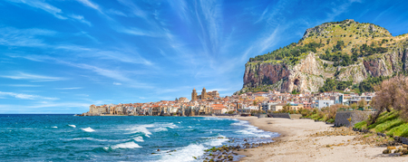 Long sandy beach and blue sea in Cefalu, town in Italian Metropolitan City of Palermo located on Tyrrhenian coast of Sicily, Italy. Cefalu is popular travel destination in Europe. Stock Photo