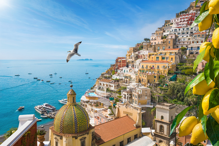 Beautiful Positano with comfortable beaches and clear blue sea on Amalfi Coast in Campania, Italy. Amalfi coast is popular travel and holyday destination in Europe. Ripe yellow lemons in foreground. Stock Photo