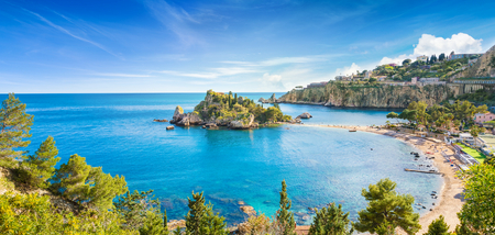 Panoramic view of Isola Bella small island near Taormina, Sicily, Italy. Narrow path connects island to mainland Taormina beach surrounded by azure waters of the Ionian Sea.