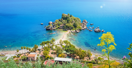 Aerial panoramic view of Isola Bella small island near Taormina, Sicily, Italy. Narrow path connects island to mainland Taormina beach surrounded by azure waters of the Ionian Sea.