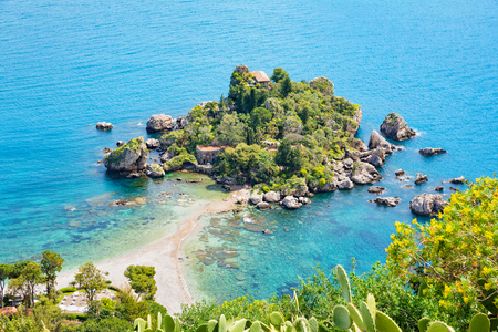 Aerial view of beautiful Isola Bella small island near Taormina, Sicily, Italy. Narrow path connects island to mainland Taormina beach surrounded by azure waters of the Ionian Sea. Stock Photo
