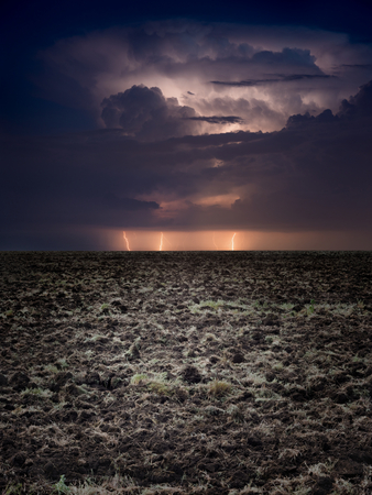 Powerful lightnings in dark stormy sky above plowed farm field, climate change and weather forecast concept