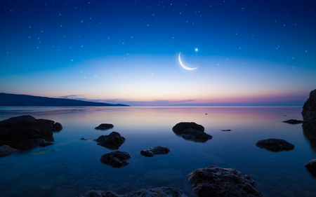 Ramadan Kareem background with crescent and stars above serene sea. Elements of this image furnished by NASA